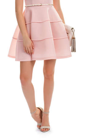 Lady wears salmon dress. Short dress and beige heels. Evening dress from famous designer. White leather purse and belt.