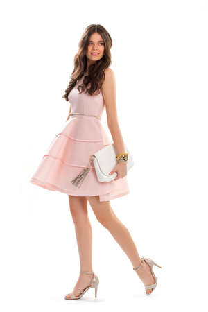 sleeveless dress: Woman in short salmon dress. Attractive girl is smiling. Sleeveless dress with folds. Young model wears evening outfit.