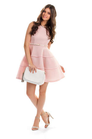 sleeveless dress: Young woman in salmon dress. Slim girl is smiling kindly. Sleeveless dress with small belt. Model wearing designer clothes.