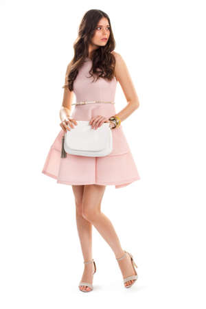 cotton dress: Young woman wears salmon dress. Heel shoes and white handbag. New fashionable clothing. Cotton dress and leather belt. Stock Photo