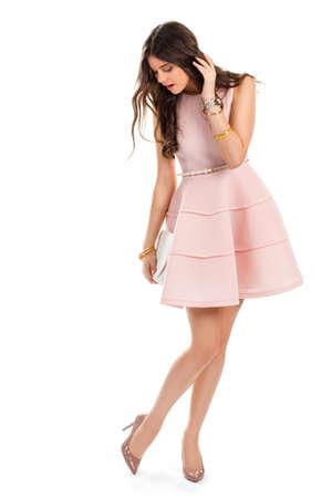 Meisje draagt roze jurk. Donker beige hakken. Glanzende schoenen en korte jurk. Nieuw en glanzend.