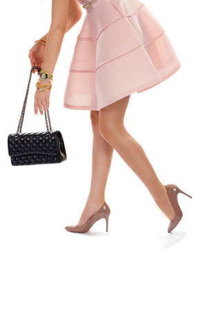 heel strap: Womans hands with black handbag. Heel shoes and light dress. Dark bag with chain strap. Glossy footwear and wrist watch. Stock Photo