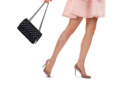 heel strap: Legs in beige heel shoes. Ladys bag with chain strap. Expensive leather accessory. Glossy heels and pink dress.
