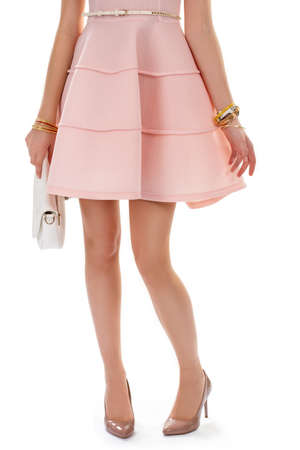 Lady in beige heel shoes. Salmon dress and coloful bracelets. Expensive glossy footwear. White handbag and leather belt.