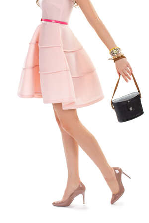 heel strap: Woman in glossy heel shoes. Salmon dress with colorful belt. Vintage leather bag and watch. Stylish spring outfit.