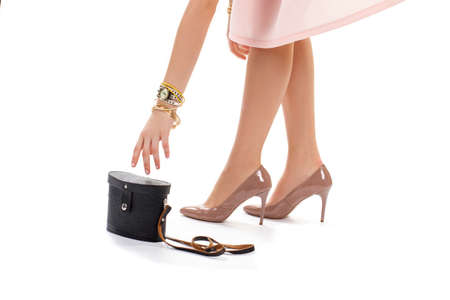might: Ladys hand reaching for bag. Glossy heels and black handbag. She nearly lost her purse. This might come in handy.