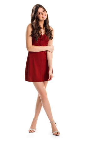 neckline: Girl in short red dress. Woman in heels smiles kindly. Cotton dress with keyhole neckline. Modesty and charm. Stock Photo