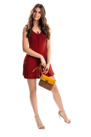 sleeveless dress: Girl in red sleeveless dress. Keyhole dress and bag. Evening outfit with accessories. Model wears beautiful summer clothes.