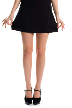 evening wear: Woman holds dress with hands. Legs in black shoes. Suede footwear and cotton garment. Beautiful evening wear.