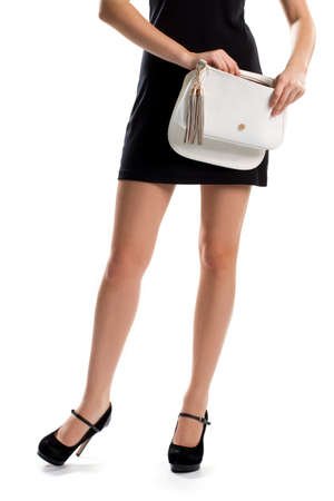 black heels: Lady in black heels. Womans hands open white bag. Suede footwear and leather purse. New accessory from famous brand.