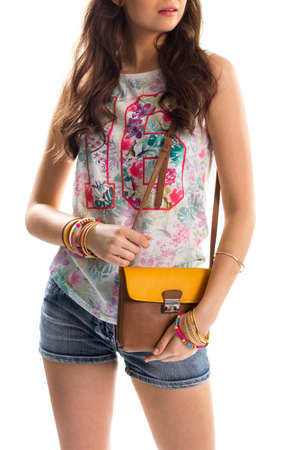 sleeveless top: Woman in printed tank top. Sleeveless floral top and shorts. Young model holds stylish handbag. Comfortable summer outfit.