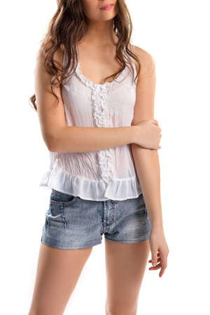 Young woman in white top. Denim shorts and sleeveless blouse. Simple and attractive outfit. High-quality cotton fabric.