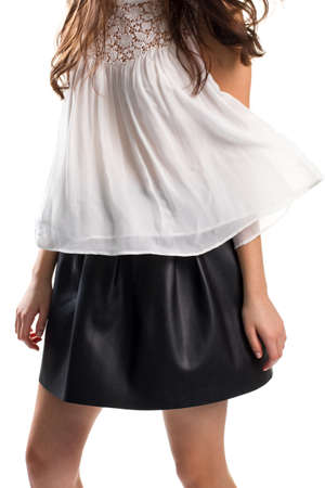 Lady in short black skirt. White blouse in the wind. Lightness of spring. New collection of female apparel.