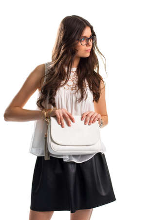 Girl in glasses holds purse. Short white blouse and skirt. Cute model wears leather skirt. Expensive-looking outfit with bijouterie. Stok Fotoğraf