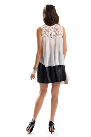 short skirt: Woman wears short skirt. Back view of white blouse. Trendy apparel from boutique. Small wrist watch. Stock Photo