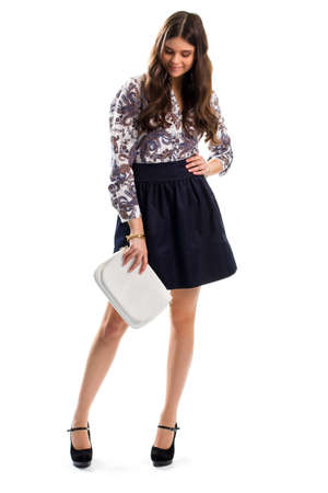fits in: Girl in floral shirt smiling. Woman looks at her shoes. Handbag and dark navy skirt. New footwear fits perfectly.