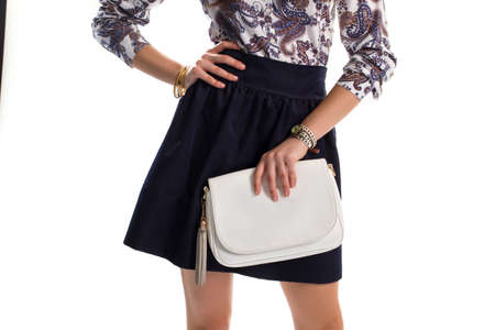 White handbag in ladys hand. Watch and dark navy skirt. Stylish accessories for evening outfit. Cotton clothes with leather purse.