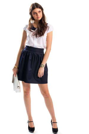 clutch bag: Lady in navy skirt. Clutch bag and heel shoes. Cotton blouse with short sleeves. How to look attractive. Stock Photo