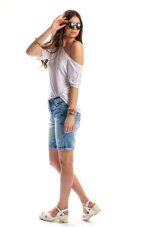 tunic: Girl in white tunic. Lady touching her sunglasses. Side view of denim shorts. Simple clothes that looks good. Stock Photo