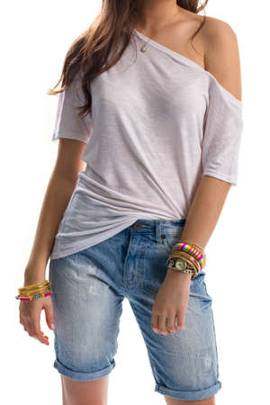 tunic: Lady wears long denim shorts. White tunic and colorful bracelets. Casual outfit for summer. Look good on vacation. Stock Photo