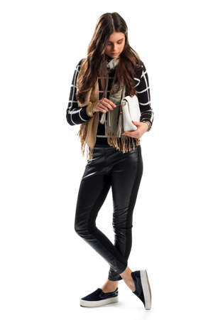 inserts: Girl touches white clutch bag. Sweatshirt and beige scarf. Trendy slip on shoes. Leather pants with side inserts.
