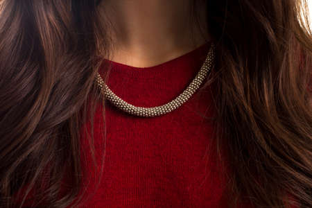 precious metal: Accessory on ladys neck. Red garment and necklace. Custom made jewelry of silver. Precious metal and quality fabric.