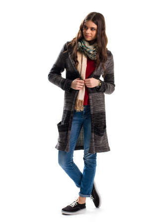 outerwear: Lady in dark sweater coat. Printed scarf and denim pants. Woolen outerwear for autumn. Model wears new garment. Stock Photo