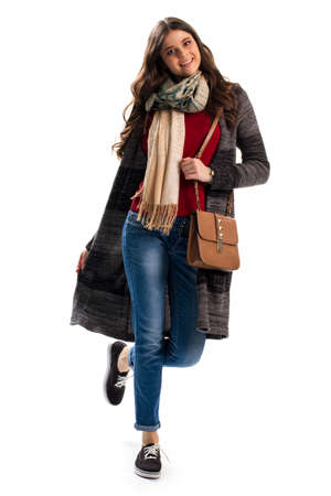 outerwear: Woman in sweater coat. Brown handbag and blue jeans. Autumn outfit with stylish scarf. New outerwear and accessories. Stock Photo