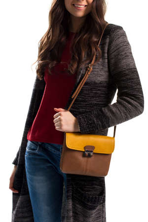 outerwear: Young woman in sweater coat. Brown and yellow bicolor purse. Warm outerwear and simple jeans. Casual autumn style.