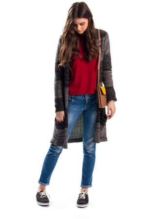 outerwear: Lady in long sweater coat. Jeans and handbag with strap. Woolen outerwear and canvas shoes. Casual outfit from lookbook.