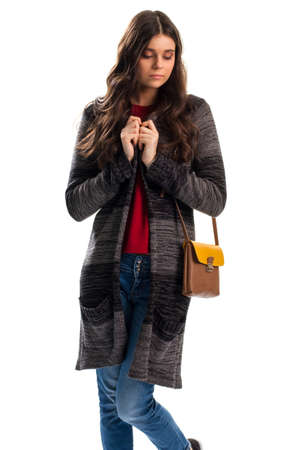 cold background: Woman in long outerwear. Striped sweater coat and jeans. When its cold outside. Feeling of loneliness. Stock Photo