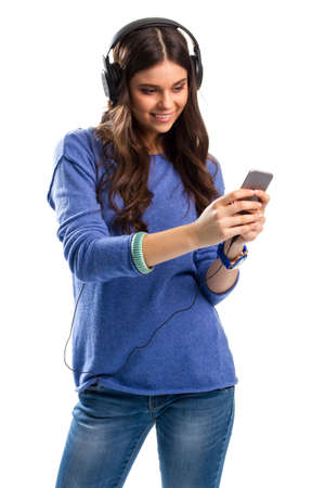 durable: Smiling woman with headphones. Lady looks on cell phone. Tons of new impressions. New durable headphones. Stock Photo