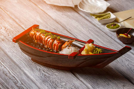 shrimp boat: Sushi boat on wooden surface. Sushi rolls and cooked shrimp. Breakfast in japanese cafe. Small portion of seafood.