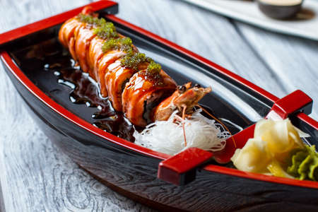shrimp boat: Sushi boat with a shrimp. Sushi rolls and white noodles. Uramaki rolls in soy sauce. Japanese seafood in local restaurant.