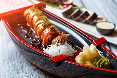 shrimp boat: Shrimp on sushi boat. Sushi rolls and wasabi. Uramaki rolls with green caviar. Traditional recipe from japanese cuisine.