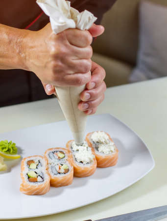 adds: Plate with sushi rolls. Man holds pastry bag. Chef adds fresh cream cheese. Decoration of uramaki rolls.