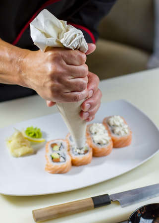 pastry bag: Sushi rolls on a plate. Mans hand with pastry bag. Uramaki rolls with cream cheese. Delicacy cooked at japanese restaurant.