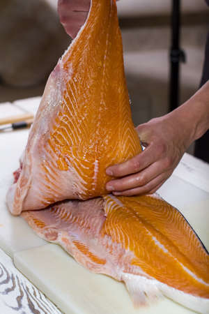 boneless: Male hands hold fish meat. Cooking board with boneless fish. Salmon for a pie. Butcher working in the kitchen.