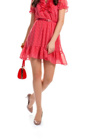 Girl wearing red dress. Young woman on heels. Small leather belt. Fashion model on white background.