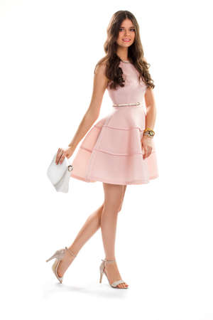 cotton dress: Lady in short salmon dress. Smiling girl on white background. Leather purse and cotton dress. Beautiful and charming model.