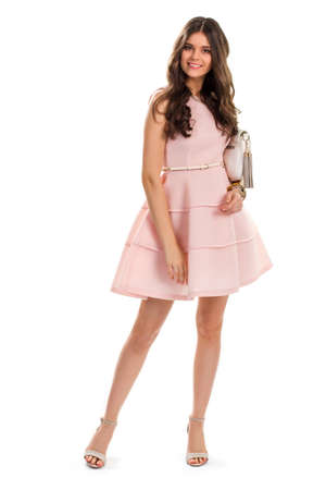 designer bag: Lady in salmon evening dress. Young woman is smiling happily. Model wears attractive clothes. Designer dress and new bag.