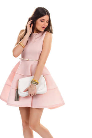 shy girl: Lady wears light pink dress. Sleeveless dress and white bag. Shy girl on white background. Beauty and modesty. Stock Photo