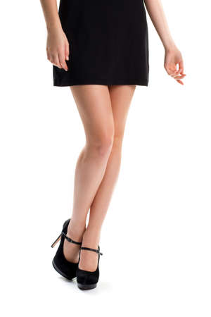 evening wear: Girls legs in black heels. Short dress and footwear. Luxury and expensive suede shoes. New collection of evening wear.