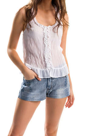 Woman in white blouse. Sleeveless top and short shorts. Light apparel for summer. Model wears cotton clothing. Stok Fotoğraf