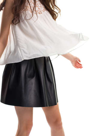 leather skirt: Woman in short black skirt. Blouse in the wind. Garment made of light material. Cotton top and leather skirt.