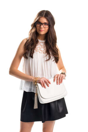 Woman in sleeveless blouse. Lady in glasses holds purse. Pretty girl on blank background. Leather skirt and expensive bracelets. Stok Fotoğraf