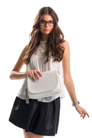 Young woman in blouse. Sleeveless white top and glasses. Plain purse and bracelets. Leather skirt of high quality. Stok Fotoğraf