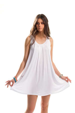 simple girl: Girl in short white sarafan. Set of bright-colored bracelets. Simple clothing for warm season. Youth and purity.