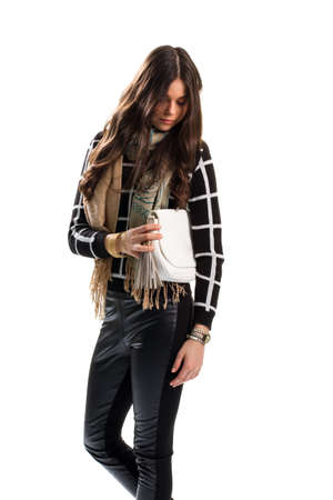 checkered scarf: Woman touches white clutch bag. Beige scarf and black pants. Autumn look with stylish accessories. Brand new purse.