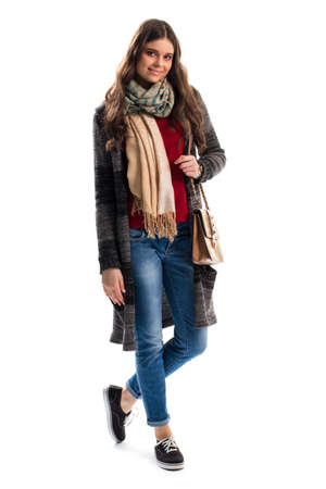 outerwear: Woman in sweater coat smiling. Beige scarf and black shoes. New stylish outerwear for spring. Feel warm and comfortable.